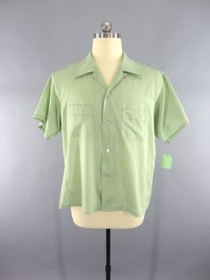 Preppy vintage 1960s men's shirt. Light green with front pocket and small embroidered design. In excellent condition. Made of cotton / polyester by Grant-Crest Menswear. Tag size XL 17 - 17 1/2. Pleas