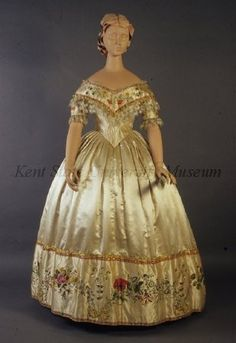 Dress Date	1853-1857, ca. Culture	American, attributed Description	Off-white silk satin. Bodice: wide neck, short sleeves, handpainted flowers trimmed with blonde lace. Full skirt with handpainted border, metallic bows.