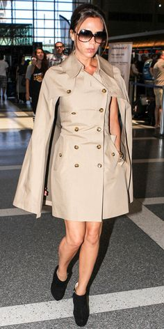 Victoria Beckham flew out of LAX in a caped trench, oversized sunglasses, a gold watch and ankle boots.
