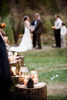 rustic wedding: stumps as an aisle runner with mason jars filled with candles