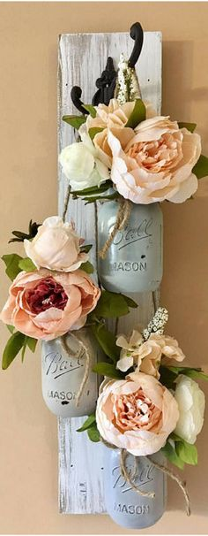 Distressed Mason Jar Sconces that give the illusion of climbing roses are the perfect unique piece of wall art! Trying to achieve that farmhouse look? This gorgeous mason jar teardrop sconce is a teardrop piece that comes with 3 floral units filled with peonies and wild flowers. Lovely for a housewarming gift.