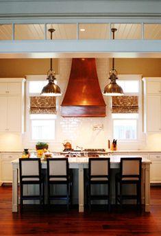 Elegant copper range hood looks great with beautiful wood floors