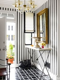 "A white Roman shade bordered in black adds more graphic punch to the foyer. ""The house makes you want to put on some Chet Baker and get all Mad Men with a pack of cigarettes and a shaker full of gin martinis,"" says Thomas.   - HouseBeautiful.com"