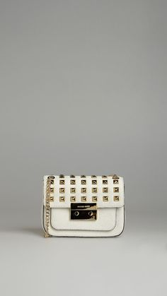 Sloan stud white leather small shoulder studded flap bag, metal and leather shoulder strap,logoed lock closure, monogram lining, three internal pockets, six card slots, front pocket, 8x5.5x2.5 inch - 20x14x6.5 cm.