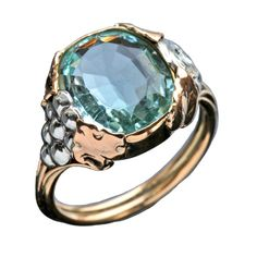 Arts & Crafts ring 'Wine Roses' A specially commissioned early 20th century ring in two color gold with a 5 carat aquamarine with symbols of grapes a rose. Hieroglyphic style cartouche containing the planetary symbols of Jupiter, Venus Mars.