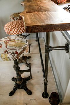 The breakfast counter is a wood slab that sits on thrifty plumbing pipes. Swiveling stools were scored at a flea market for $200 and upholstered in outdoor fabric.