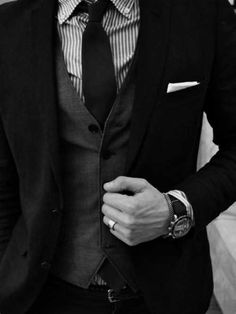 The complete Look! black suit, grey waist coat, slim black tie with a pocket square. The watch also makes a statement.