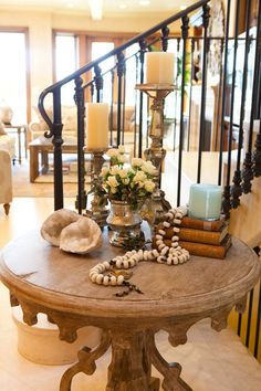 """Add unexpected pieces to a tablescape. Note the different heights, textures and shapes on this hallway table. Candlesticks, hurricanes, books, statues, small framed photos, bowls, shells, driftwood, beads and boxes are all good pieces to try. Many designers recommend arranging things in groups of three or five."""