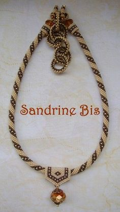 Sandrine Bis' bead crochet toggle necklace- the intertwined rings are used as the back closure.  The front focal is a beaded bail and crystal pendant.