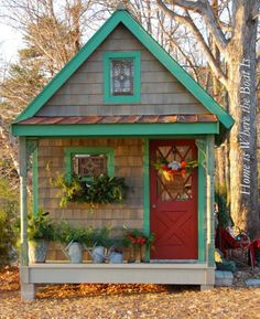 Christmas greenery tucked into window boxes, watering cans and even a pair of wellies shower this potting shed's porch with holiday cheer. Around the corner, a garden bench is decked with a cozy red blanket and surrounded by red and green gazing globes.