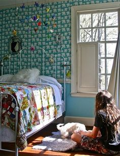 I love the little paper cranes hanging from the ceiling...I dig the crafty vibe of this room, and the quirky wallpaper.