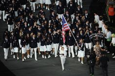 Mariel Zagunis of the United States Olympic fencing team carries her country's flag during the Opening Ceremony of the London 2012 Olympic Games at the Olympic Stadium on July 27, 2012.  Author: Edecio Martinez  Credit: Stu Forster/Getty Images