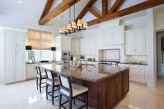 A white kitchen with cathedral ceilings and several exposed wood beams that draw the eye upwards. The same color wood is used in the island,which is topped by light brown granite. The cream tile floors look nearly white in the sunlight.