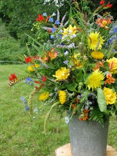 yellow dahlias and roses, red crocosmia, peachy-orange alstroemeria, and blue delphiniums in a metal bucket