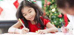 Young girl in front of holiday decorations writing a letter.