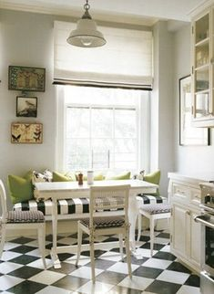 Beautifully proportioned banquette, chairs and artwork around large window.
