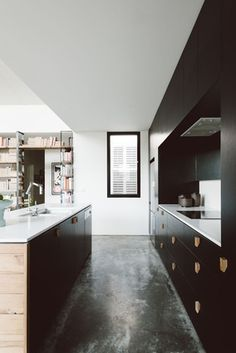 Burnished concrete floors and black cabinetry make for a modern kitchen.  Northrop House by Techne Architects