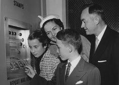"On February 11, 1956, the Post Office Department unveiled the Model ""F"" Stampmaster at the McLean, Virginia, Post Office. Ted Stans, the 12-year-old son of Deputy Postmaster General Maurice H. Stans, tried it first. The machine not only made change but also ""spoke"" to customers with pre-recorded messages at the end of transactions."