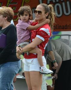JLo rocks a red jersey and white short-shorts during a charity football game in San Juan, Puerto Rico. And her little son Max showed his support by donning a red-and-white checkered shirt himself.