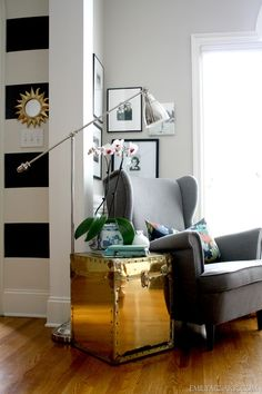 office reading nook with gray wingback chair and brass trunk