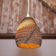 Laser-cut  pendant lamps made from repurposed cardboard boxes and hand assembled.