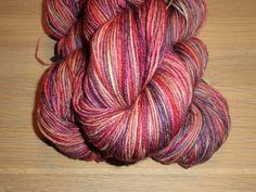 Garn i en mellemkraftig tykkelse. nok den mest populære garntykkelse til mange strikkeprojekter. Garnet et 4-trådet og velegnet til jumpere, tørklæder og alle beklædningsdele, der bæres tæt på huden, da det er meget blødt og er håndfarvet i smukke røde og lilla farver.