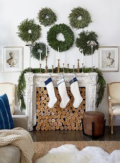 A traditional swag is paired with a gallery wall display of wreaths, collection of vintage brass candlesticks, and piles of logs are cleverly displayed inside the fireplace.