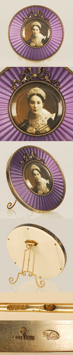 A Faberge silver and translucent enamel photograph frame, Moscow, circa 1896-1908. Circular in form, enameled in translucent lavender over a sunburst engine turned ground, with a ribbon-tied reeded border, a beaded bezel set with a bow knot at the top and bezel cut glass over the circular aperture, an ivory back and shaped silver strut.