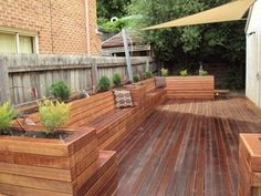 Deck with full box seating, planter boxes and a sun shade.