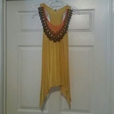 Flowy Tank Top Yellow (kind of mustard shade) flowy top. Really cute. Has lace-like overlay around the neck (orange, burgandy, and brown). The bottom of the shirt is cut longer on the sides. Racerback tank top. Good condition and from non smoking home. Tops Tank Tops