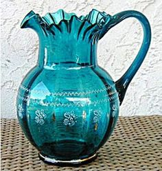 teal glass pitcher; red flowers for centerpiece in teal pitcher. ..
