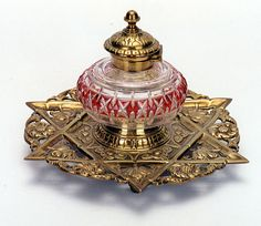 A FRENCH BRASS INKWELL, footed and pierced with star of David design fitted with hand cut and engraved rose-red and clear crystal inkwell with original brass top. Diameter 7 in., c. 1910