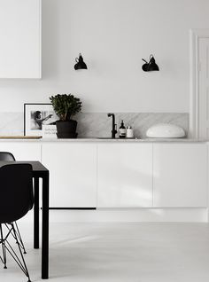 Black wall light fixture in the kitchen   Image by Kristofer Johnsson via Residence