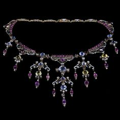 Important and unique Renaissance Revival style necklace the front decorated with a deep fringe of girandole drops with scrolls and volutes applied with black and white piqué enamel and set through-out with sapphires, rubies, chrysoberyls and diamonds Carlo & Arthur Giuliano, London circa 1895
