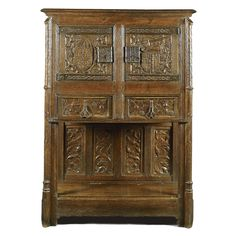 A French Gothic carved oak dressoir late 15th / early 16th century with a later moulded top above a pair of doors, the left with a coat of arms with seven fleur-de-lys amongst vine-leaves and grapes, the right with the coat of arms of France with fleur de lys with an arm holding an axe amongst scrolling vines, with pierced tracery lockplate and hinges above two frieze drawers, the sides with three linenfold panels the stiles with leaf carved buttresses the backboard with four panels