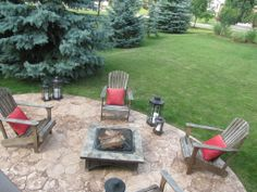 A stamped concrete patio gives you the look and texture of a stone patio. We love this concrete stamped patio with firepit, adirondack chairs and metal lanterns.