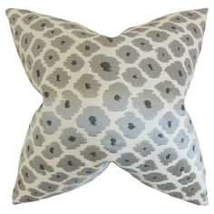 Add a pop of style to your favorite chaise or arm chair with this lovely pillow, showcasing a stylized floral motif in gray and black.