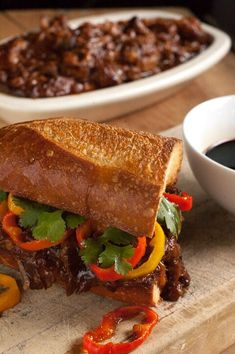 These balsamic bbq pulled pork sandwiches cook in the slow cooker all day in tangy bbq sauce, get piled on a crispy bun with caramelized sweet peppers and then dipped into tangy balsamic vinegar. This easy slow cooker recipe is basically heaven in your mouth.