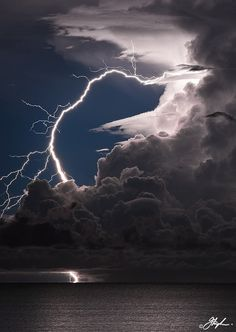 i love lightning because it never looks the same as another flash. this photo is beautiful the way the lighning strings bend away from the clouds and strands fall off and away from the main strike and then gets covered by the clouds and then is shown hitting the water-k