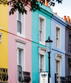 Sherbet-coloured buildings line London's famous Portobello Road in the Notting Hill district. The bustling market is renowned for antiques, fashion, food and other treasured finds.