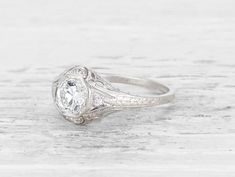 Antique Edwardian engagement ring featuring an approximately 0.70 carat old European-cut diamond with EGL certificate stating the diamond is F - G color/SI1 clarity, accented with 4 single-cut diamonds in a filigree mount. Set in platinum.Circa 1915 This handmade mounting showcases fine Edwardian craftsmanship with de