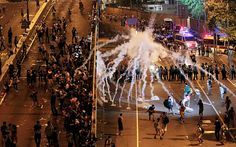 Umbrella Revolution Hong Kong, Riot police fire tear gas on student protesters occupying streets surrounding the government headquarters in Hong Kong, early Monday, Sept. 29, 2014.