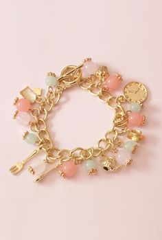 Tea Time Charm Bracelet- A feminine bracelet that features tea leaves detailed toggle clasp, tea party themed charms, and a harmonious combination of pink, mint green, and white translucent beads. Charms include a tea cup, tea pot, tea bag, cupcake, clock, spoon, and a fork.  Currently on sale for $16.99