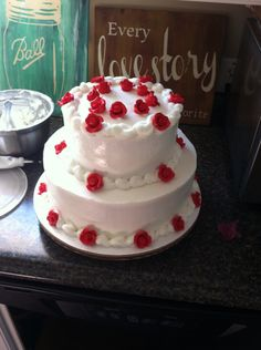 White cake, white buttercream icing, red roses wedding cake Very simple very elegant they had their own cake topper which would go inside the circle of roses on top.