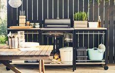 Eine dreiteilige Küche, u. a. mit einem Grill, an einem dunklen Holzzaun