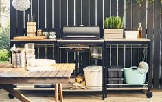 Una cuina d'exterior formada per tres mòduls, un d'ells amb una barbacoa, recolzats en una tanca de fusta negra.