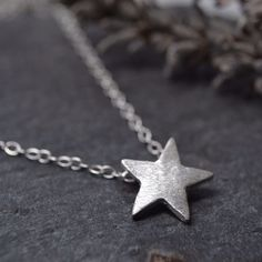 A satin finish fine silver star, on a sterling silver 16 inch chain.  The star is approx 12mm but will vary due to the nature of handmade jewellery. No two can ever be exactly the same.  I can change the necklace length if required, just let me know.  This necklace goes beautifully with these little star shaped stud earrings - which can also be made with a satin finish on request.. http://www.beckypearcedesigns.co.uk/beckypearceshop/prod_2378010-Fine-silver-teeny-tiny-sta...