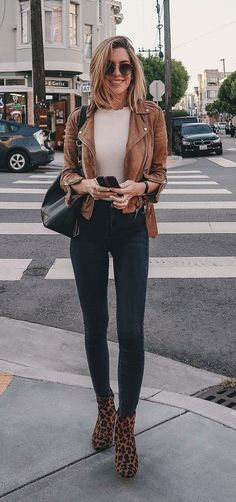 Básica e cool: 9 formas de dar um up na calça jeans. Jaqueta de couro caramelo, blusa branca, calça skinny azul marinha, ankle boot de animal print