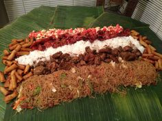BOODLEFIGHT BUFFET: banana leaves, lumpias, chopped up red egg, tomato and onion combo, rice and pansit.