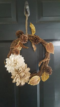 Fall/winter wreath made with grape vines, burlap flowers, leaves and pine cones. We did a crochet wreath hanger that's detachable. The entire wreath is designed to be able to be switched out with the seasons.